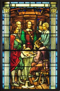 Stained Glass Window Mayflower Compact Signing. Four men and one woman standing around a man signing the Mayflower Compact.